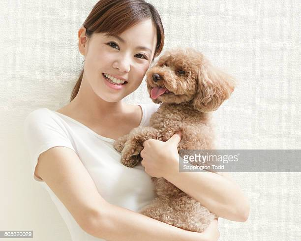 woman holding toy poodle - barboncino toy foto e immagini stock