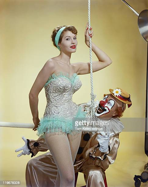 woman holding trapeze bar with clown, smiling - trapeze artist stock photos and pictures