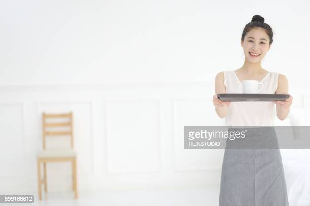 woman holding tray and coffee at home
