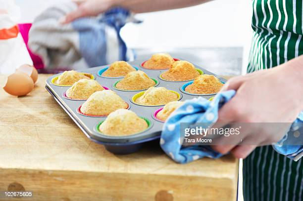 woman holding tray of cupcakes