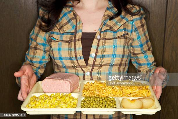 Woman holding tray of food, mid section