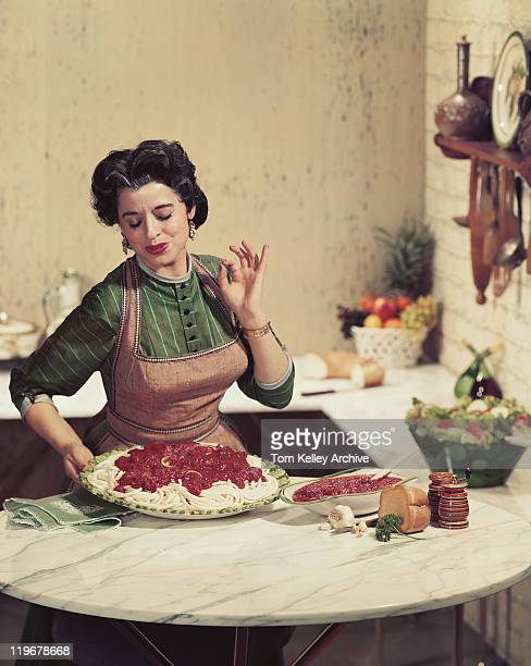 Woman holding tray of noodles and gesturing