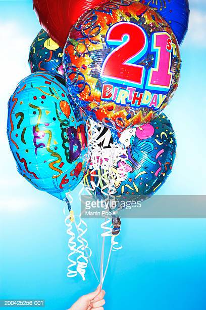 Woman holding twenty first birthday balloons