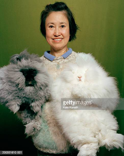 Woman holding two Angora rabbits, portrait, smiling