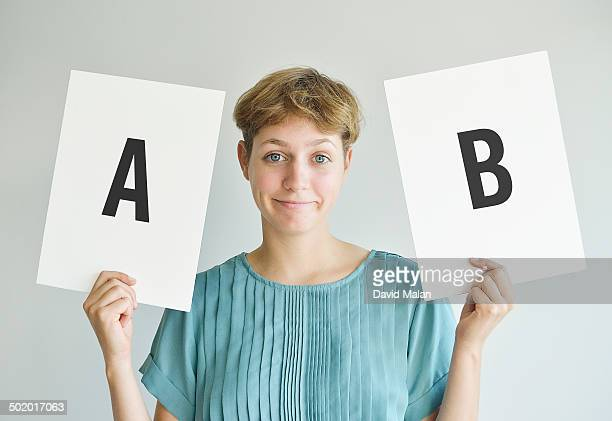 Woman holding two boards marked A & B