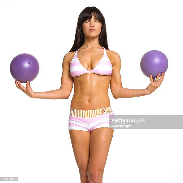 Woman Holding Two Exercise Balls