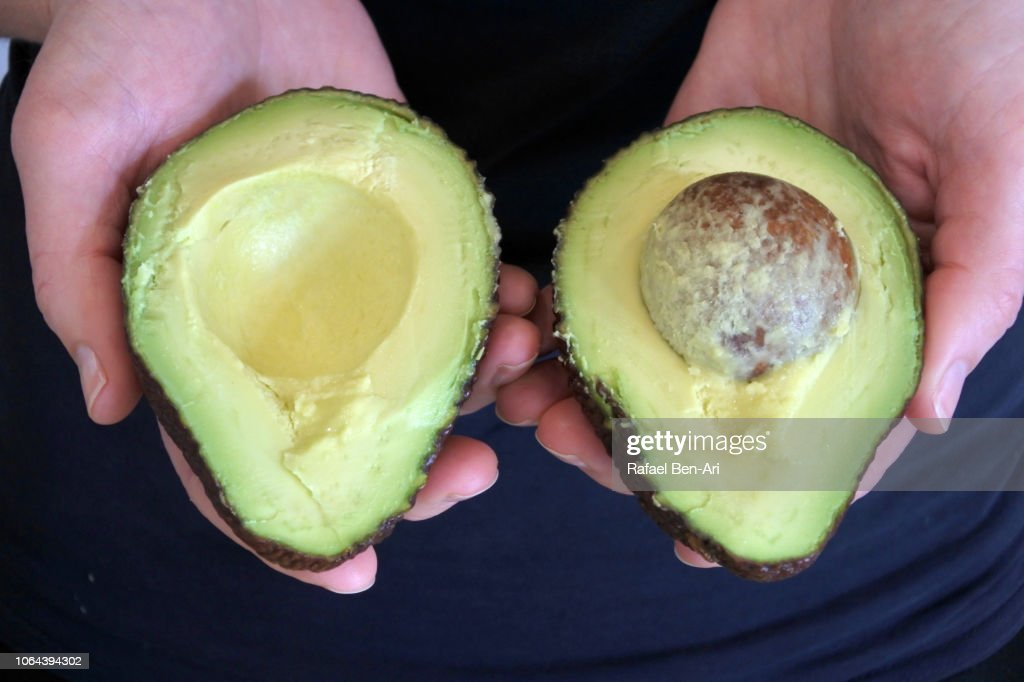 Woman Holding Two Half of Cut Avocado Fruit : Stock Photo