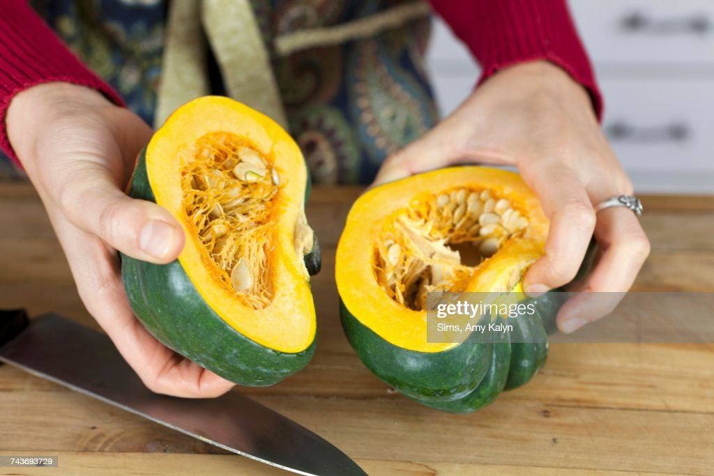 A woman holding two halves of acorn squash : Stock Photo