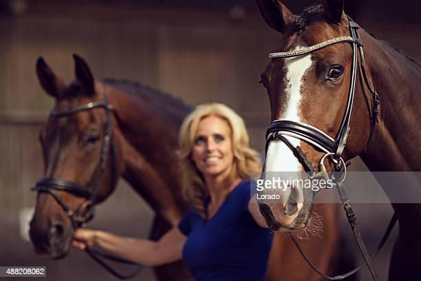 Frau hält zwei Pferde