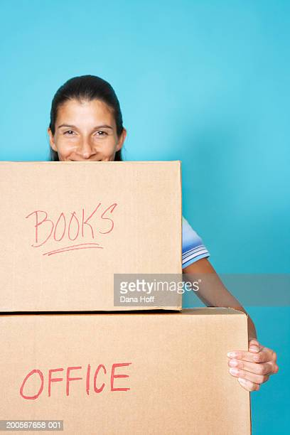 Woman holding two large cardboard boxes, smiling, portrait