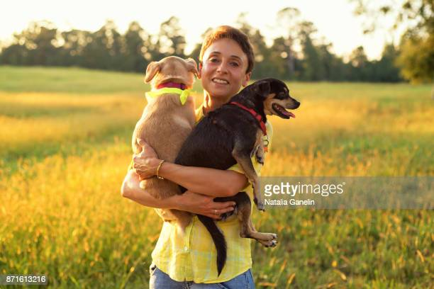 woman holding two small dogs in summer field - tame stock photos and pictures