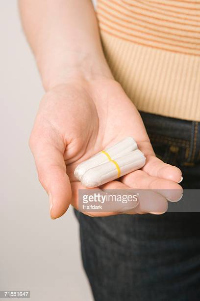 A woman holding two tampons