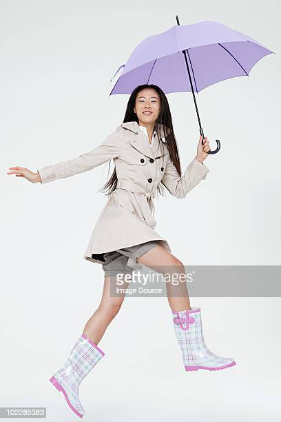 Woman holding umbrella and jumping