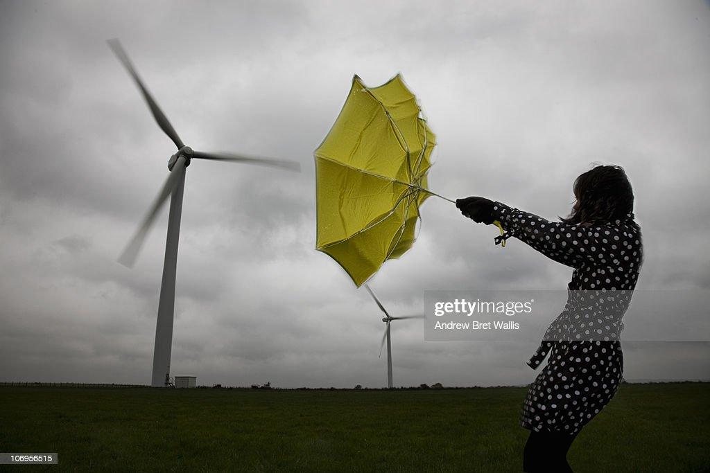 woman holding umbrella beneath wind turbines : Stockfoto