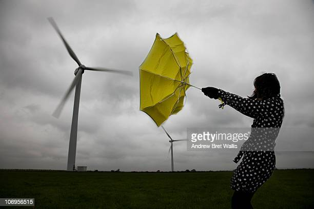 woman holding umbrella beneath wind turbines