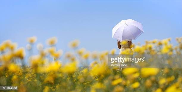 Woman holding umbrella in field of yellow flowers