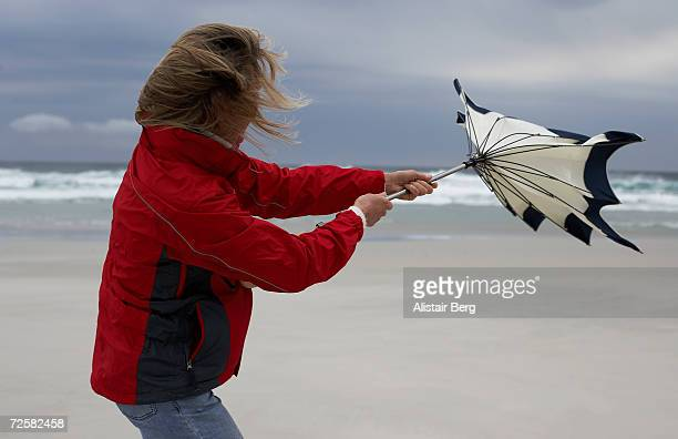 Woman holding umbrella on beach, struggling against wind