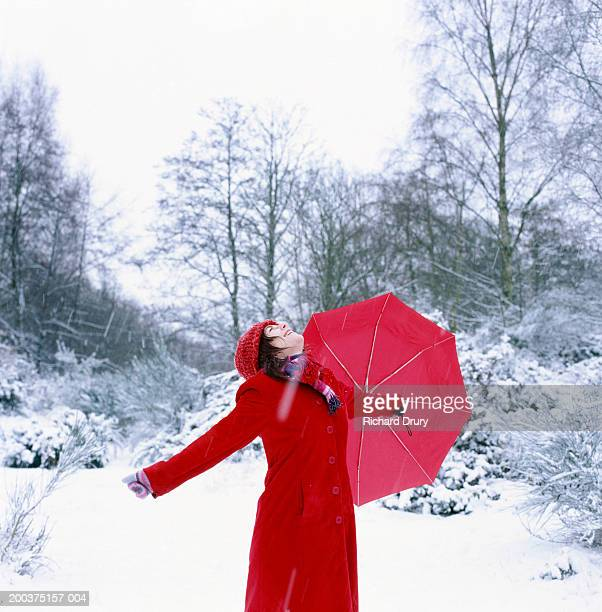 Woman holding umbrella outdoors, arms outstretched looking up, winter