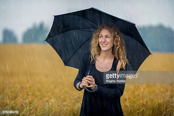 woman holding umbrella - windbreak stock pictures, royalty-free photos & images
