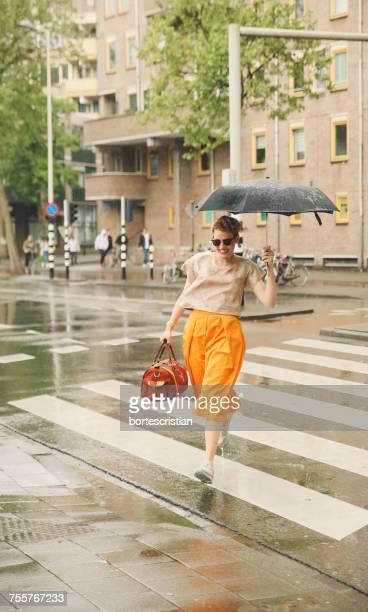 woman holding umbrella - bortes foto e immagini stock