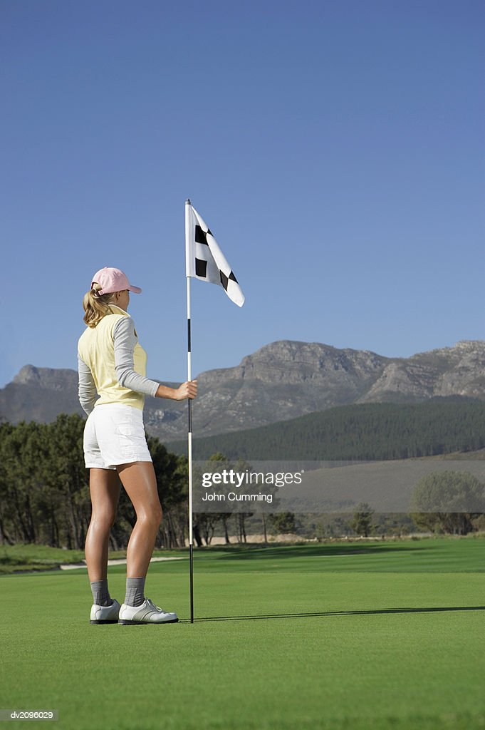 Woman Holding up a Flag on a Putting Green : Stock Photo