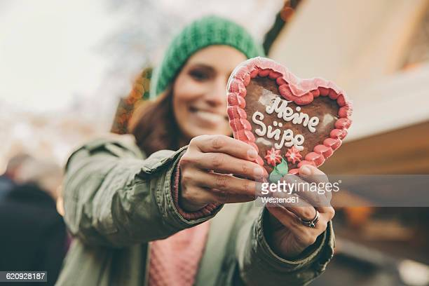 Woman holding up a gingerbread heart on the Christmas Market