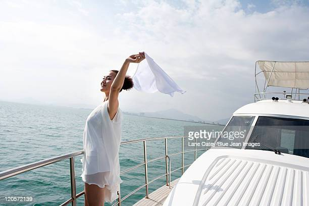 Woman holding up a Scarf in the Wind