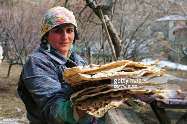 Woman holding up a stack of traditional Armenian bread Bjni Armenia