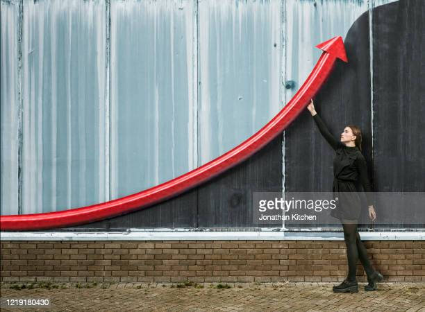 woman holding up arrow - instrument of measurement stock pictures, royalty-free photos & images