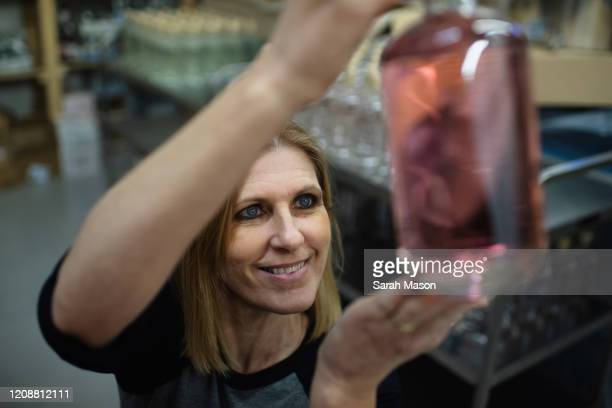 woman holding up bottle of pink gin and smiling - femalefocuscollection stock pictures, royalty-free photos & images