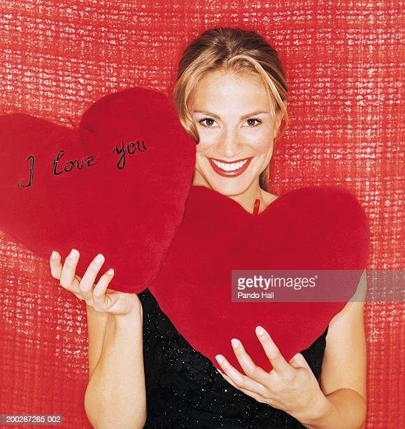 woman holding up cushions, one saying 'i love you', smiling, portrait - i love you photos et images de collection