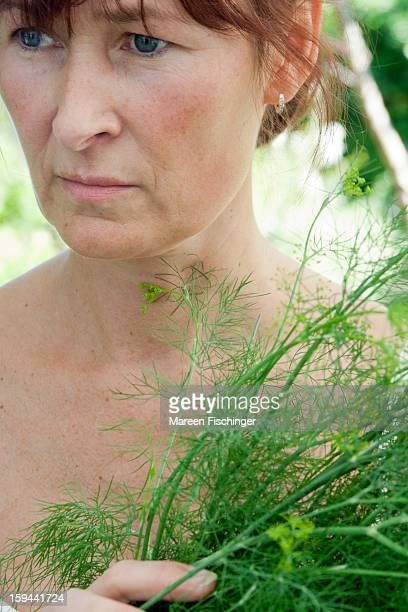 Woman holding up dill in her garden, looking away