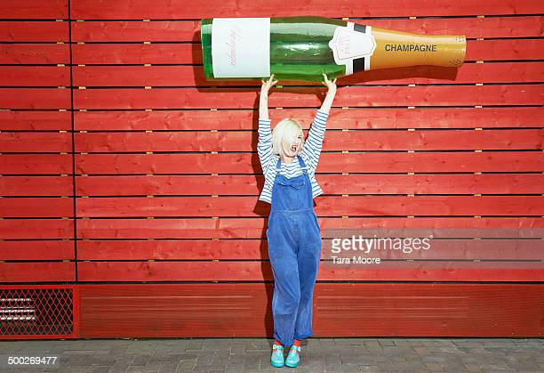 woman holding up giant champagne bottle