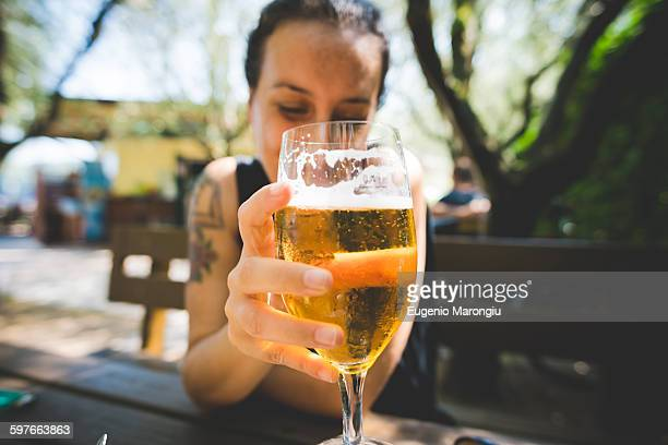 Woman holding up glass of beer, Garda, Italy