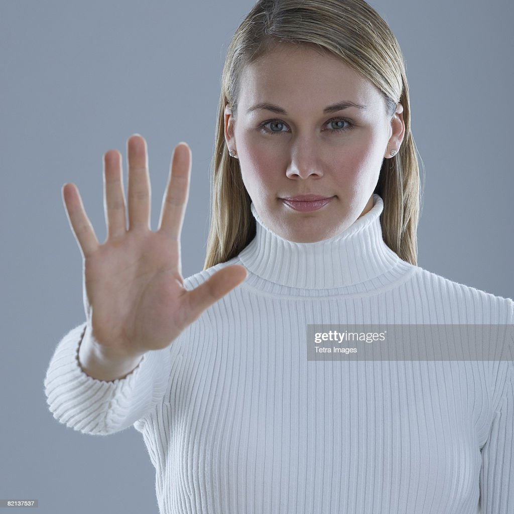 Woman holding up hand with palm out : Stock Photo