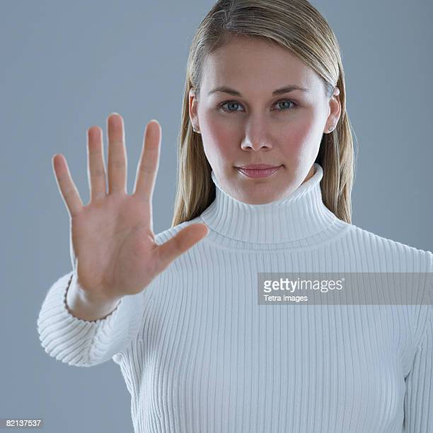 Woman holding up hand with palm out