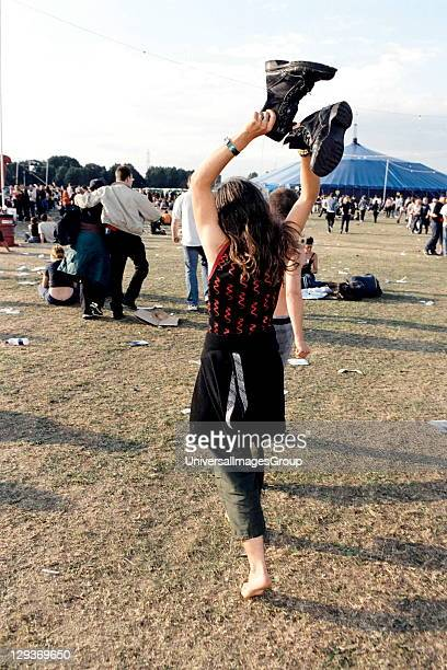 A woman holding up her big boots dancing around Festival Hackney Wick London 1990's