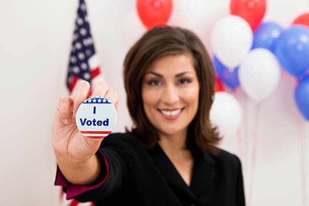 Woman holding up I voted button
