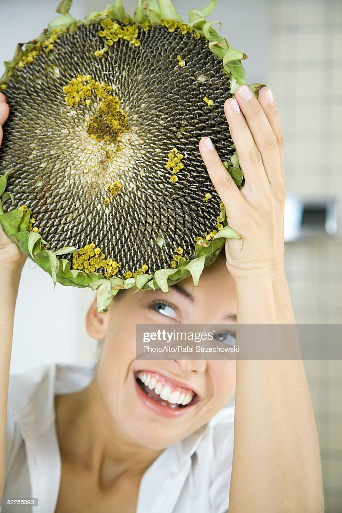 Woman holding up large dried flower head, looking up, smiling : Stock Photo