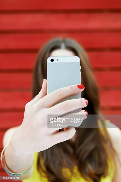 woman holding up phone to take selfie