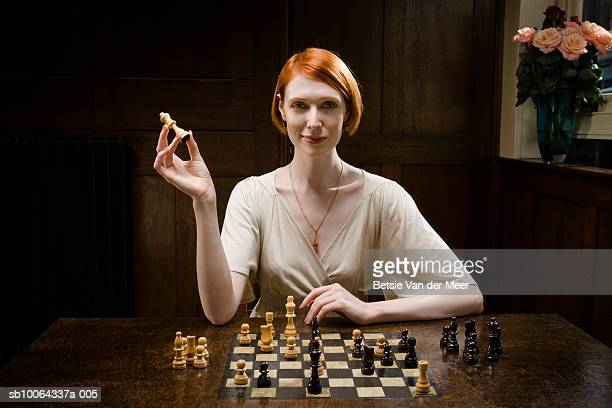 woman holding up queen chess piece, smiling, portrait - chess stock pictures, royalty-free photos & images