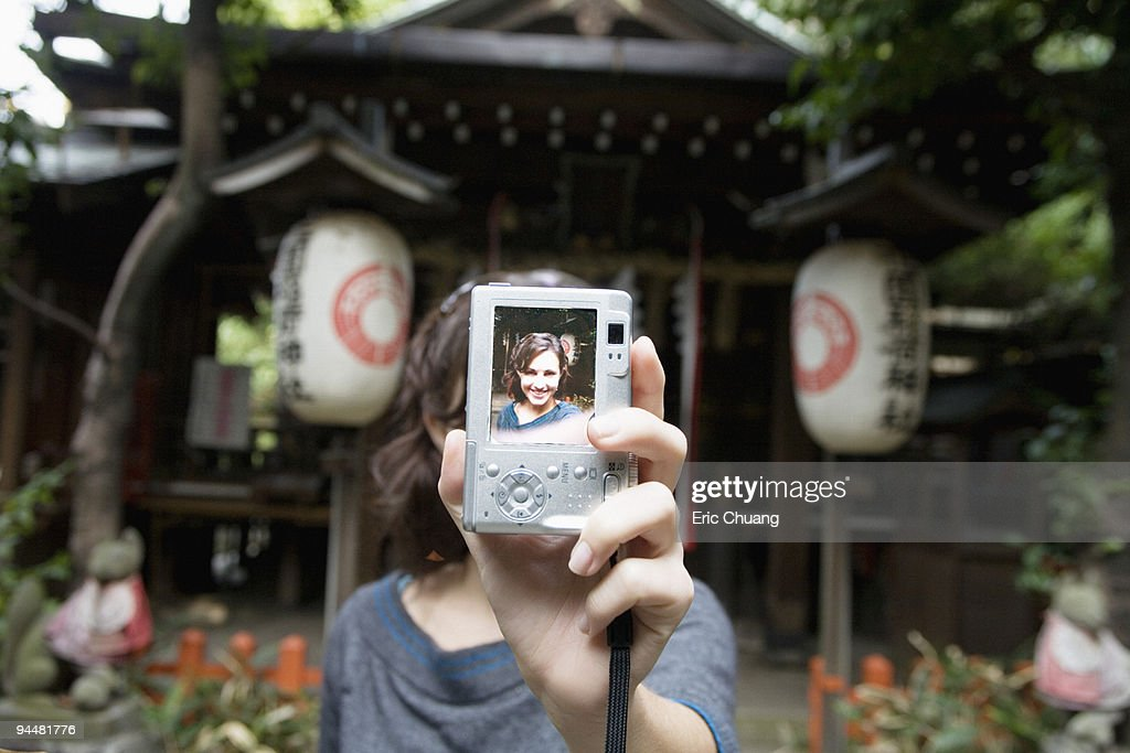 Woman holding up self-portrait in digital camera, Japan : Stock Photo