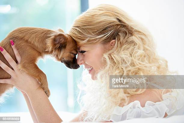 Woman holding up small dog nuzzling noses