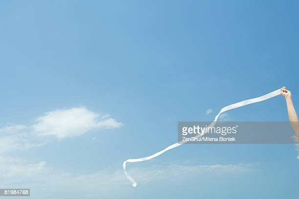 woman holding up streamer against blue sky, cropped view - streamer ストックフォトと画像