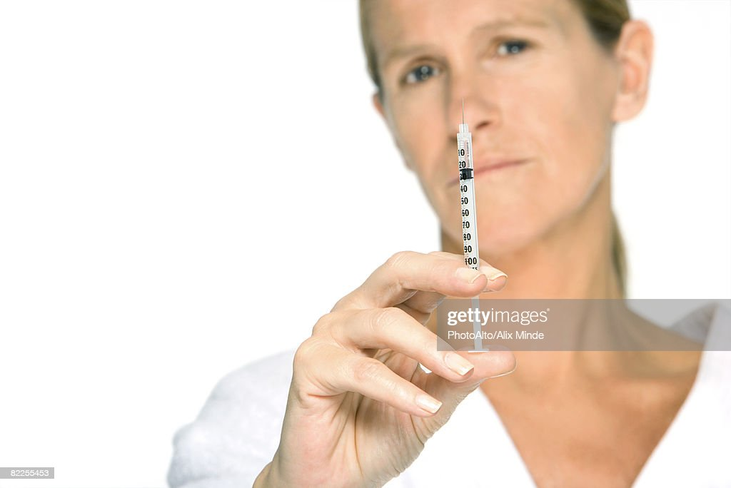 Woman holding up syringe, looking at camera : Stock Photo