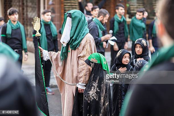A woman holding up the Hamza/Fatima's hand which represents abundance Thousands of mourners walk to commemorate the death of Husayn ibn Ali the...