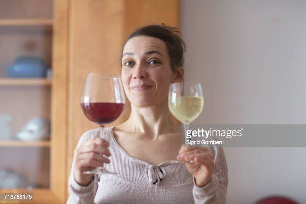 woman holding up two glasses of red and white wine - sigrid gombert stock-fotos und bilder