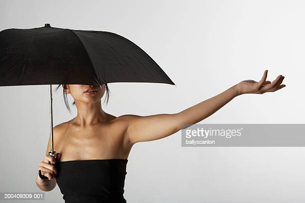 Woman holding up umbrella and arm