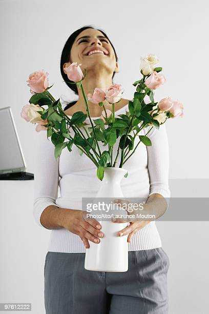 Woman holding vase of roses, smiling with head back