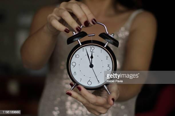 woman holding vintage alarm clock at 12 o'clock. new year's eve concept - nieuwjaarsreceptie stockfoto's en -beelden